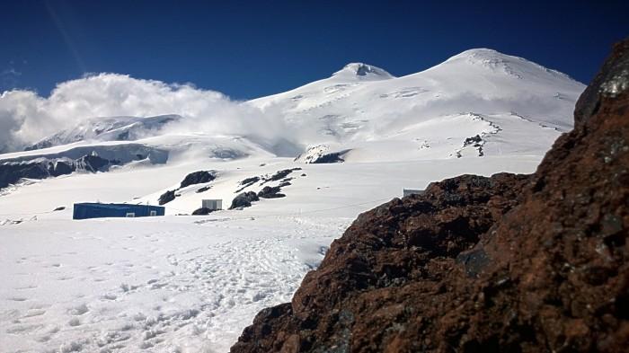 Varmer meg på lavastein med utsikt mot Elbrus